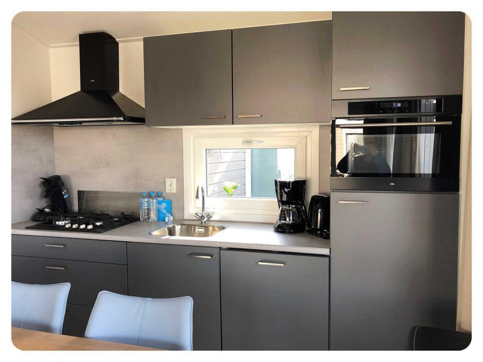 Blick auf die Küchenzeile mit Gasherd, Spülmaschine und Microwellenbackofen
